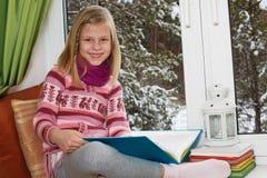 Niña que lee un libro que se sienta en la ventana en Christm Imagen de archivo libre de regalías