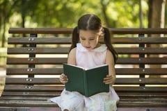 Niña que lee un libro que se sienta en un banco en el jardín Fotografía de archivo libre de regalías