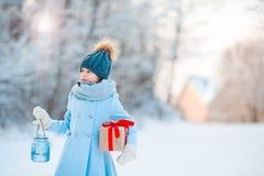 Niña que lleva a cabo la linterna y el presente de la Navidad en Año Nuevo al aire libre en día hermoso de la nieve del invierno Fotografía de archivo