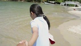 Niña que lleva a cabo la mano de su padre y que camina en la playa almacen de video