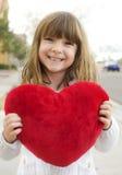 Niña que lleva a cabo un corazón rojo imágenes de archivo libres de regalías