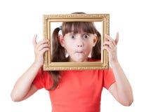 Niña que lleva a cabo un marco para los cuadros Imagen de archivo libre de regalías