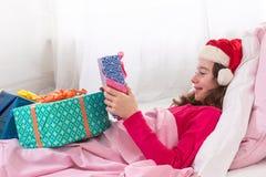 Niña que lleva el sombrero de Papá Noel que recibe su regalo Imagenes de archivo