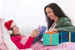 Niña que lleva el sombrero de Papá Noel que recibe su regalo Fotografía de archivo libre de regalías