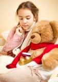 Niña que miente en cama con el oso de peluche con el tarro de la miel Fotos de archivo