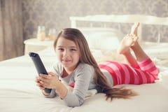 Niña que miente en cama con una TV teledirigida Imagen de archivo libre de regalías