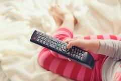 Niña que miente en cama con una TV teledirigida Fotos de archivo libres de regalías