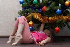 Niña que miente en ella detrás debajo del árbol de navidad Imagen de archivo libre de regalías