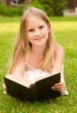 Niña que miente en hierba y el libro leído Foto de archivo libre de regalías