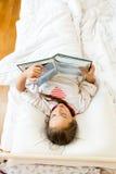 Niña que miente en la cama por mañana y que lee el libro grande Fotos de archivo