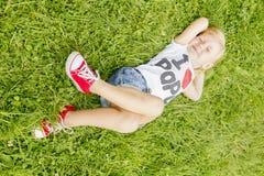 Niña que miente en la hierba y el sueño Foto de archivo libre de regalías