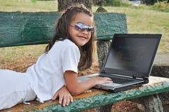 Niña que miente en un banco con su ordenador Fotos de archivo libres de regalías