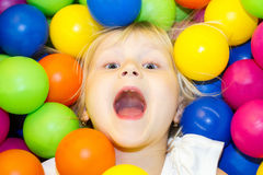 Niña que miente en una pila de bolas coloreadas Fotos de archivo libres de regalías
