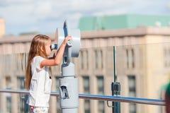 Niña que mira binocular de fichas en terraza con hermosa vista Fotos de archivo