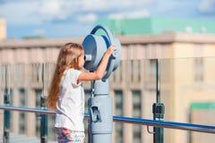 Niña que mira binocular de fichas en terraza con hermosa vista Fotografía de archivo
