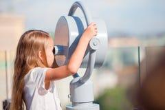 Niña que mira binocular de fichas en terraza con hermosa vista Imagen de archivo libre de regalías