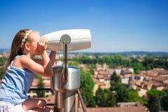 Niña que mira binocular de fichas en terraza la pequeña ciudad en Toscana, Italia Foto de archivo
