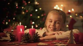 Niña que mira decoraciones de la Navidad en la tabla, centelleo de las luces en árbol almacen de video