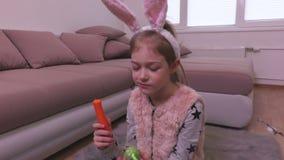 Niña que mira el huevo de Pascua decorativo y que come la zanahoria almacen de video