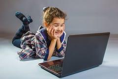 Niña que mira el ordenador portátil y el arte sonriente Foto de archivo libre de regalías
