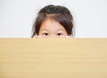 niña que mira a escondidas sobre la tabla imagen de archivo