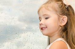 Niña que mira hacia fuera la ventana en un día lluvioso Fotos de archivo libres de regalías