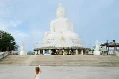 Niña que mira la estatua blanca de Buda en Phuket Fotos de archivo