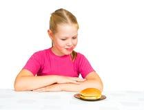 Niña que mira la hamburguesa con la lengüeta hacia fuera Foto de archivo libre de regalías