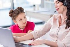 Niña que mira a la madre ocupada en las auriculares que trabajan con el ordenador portátil Fotografía de archivo