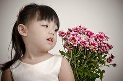 Niña que mira las flores Fotografía de archivo