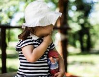 Niña que mira lejos en la naturaleza que sostiene la muñeca Foto de archivo
