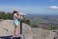Niña que mira a través de los prismáticos de visita turístico de excursión Foto de archivo libre de regalías
