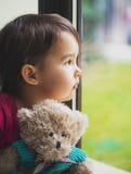 Niña que mira a través de ventana con el oso de peluche Imagen de archivo