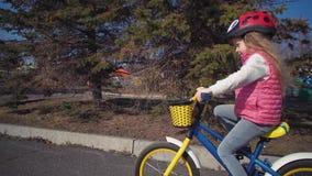 Niña que monta una bici en parque viejo almacen de video