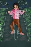 Niña que monta una bici pintada Imagen de archivo libre de regalías