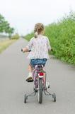 Niña que monta una bicicleta Imagenes de archivo