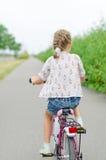 Niña que monta una bicicleta Imágenes de archivo libres de regalías