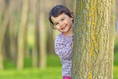 Niña que oculta detrás de un árbol Imágenes de archivo libres de regalías