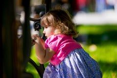 Niña que oculta detrás de un banco en el parque Foto de archivo