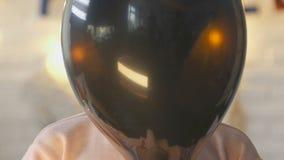 Niña que oculta detrás del globo negro, haciendo la cara asustadiza, partido de Halloween almacen de video