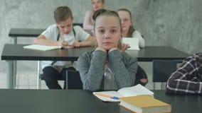 Niña que piensa difícilmente durante clase en escuela primaria almacen de metraje de vídeo