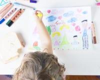 Niña que pinta un sol en un dibujo de los niños de Fam multirracial Imagenes de archivo