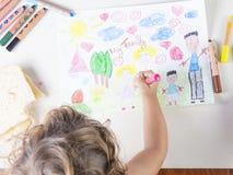 Niña que pinta un vestido rosado de una muchacha en un dibujo de los niños de Imágenes de archivo libres de regalías