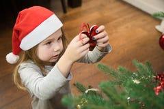 Niña que pone el corazón rojo en el árbol de navidad Foto de archivo