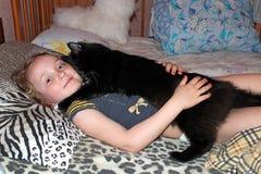 Niña que pone en cama así como su gato Así como su animal doméstico Fotos de archivo