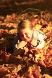 Niña que pone en hojas amarillas Imagen de archivo