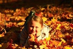 Niña que pone en hojas amarillas Fotografía de archivo libre de regalías