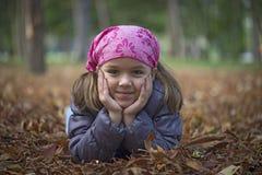 Niña que pone en las hojas de otoño Fotos de archivo libres de regalías
