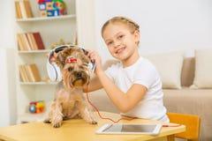 Niña que pone los auriculares en el perro Fotos de archivo libres de regalías