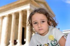 Niña que presenta delante de un templo romano Imagenes de archivo